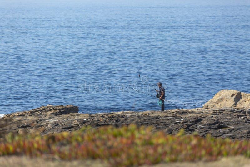 Vista no mar das águas e no penhasco das rochas, com um pescador e as varas de pesca, na costa foto de stock royalty free