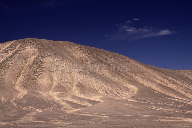 Vista no monte isolado marrom seco estéril que contrasta com o céu azul profundo em salar de atacama - Chile foto de stock