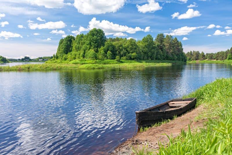A vista no rio com ilha e o barco de madeira colocou acima no riverbank foto de stock