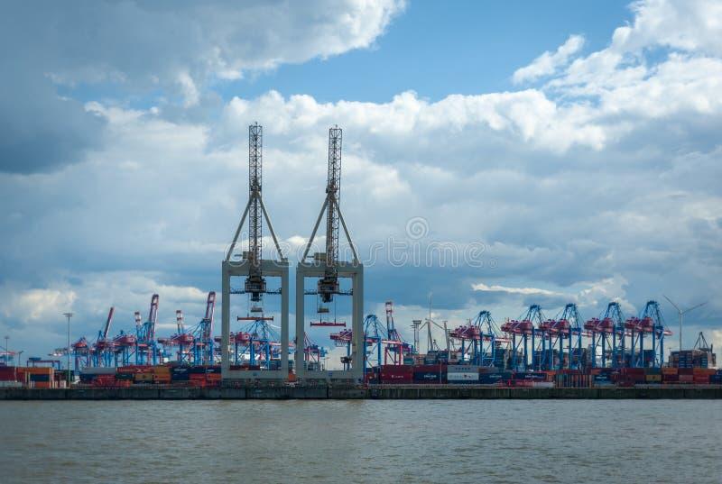 Vista no terminal de recipiente Burchardkai no porto de Hamburgo, Alemanha no dia e no céu nebuloso fotografia de stock royalty free