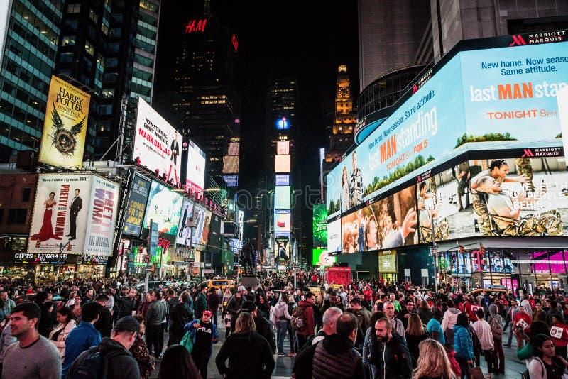 Vista nocturna de la calle del Times Square con los artistas de la calle y la muchedumbre enorme fotografía de archivo libre de regalías