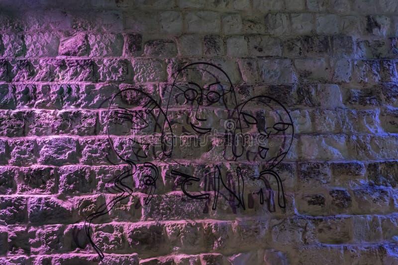 Vista nocturna de la figura del alambre de una familia con la inscripción en hebreo - regalo del cielo atado a la pared del edifi fotos de archivo