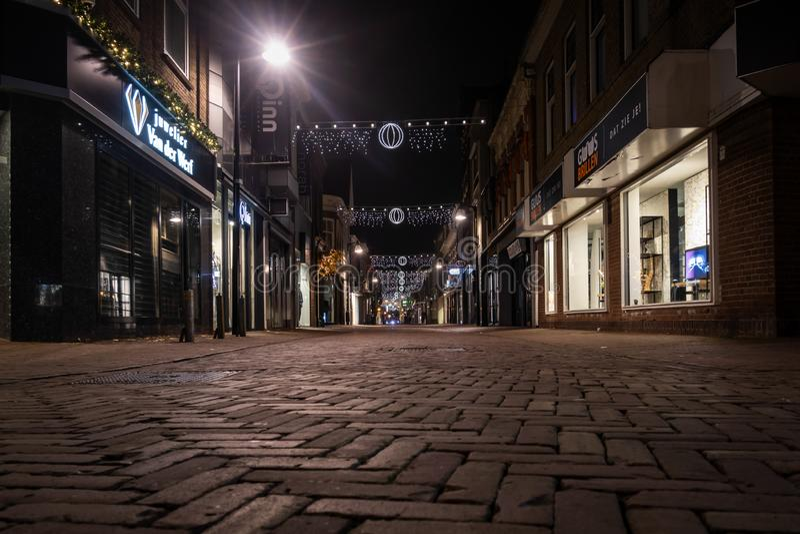 Vista nocturna de la perspectiva del ángulo bajo de una calle que hace compras adornada la Navidad vacía imagenes de archivo