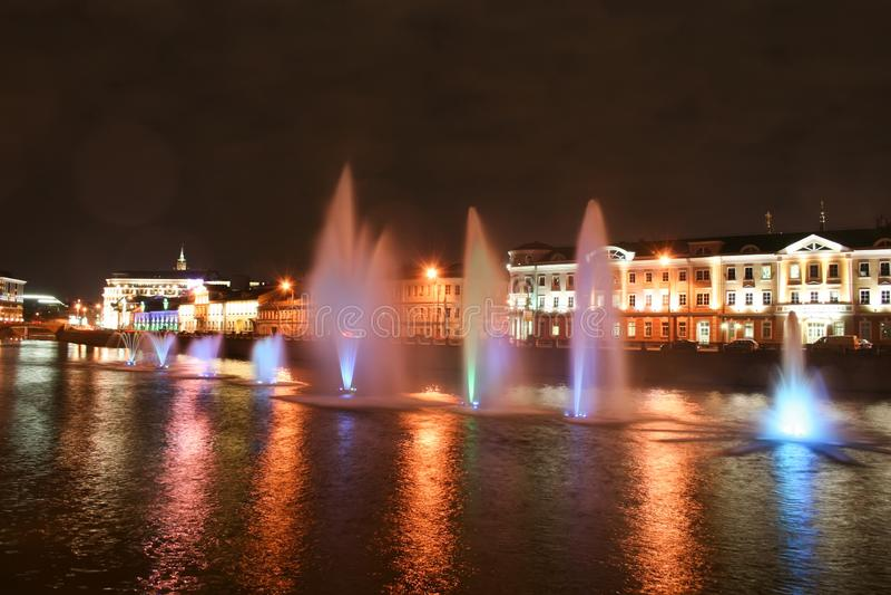 Vista nocturna de las fuentes flotantes multicoloras hermosas en el río a lo largo de la calle fotografía de archivo