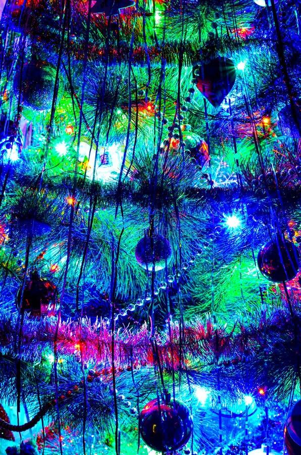 Vista nocturna de un árbol del Año Nuevo con las luces de la antorcha y las decoraciones de la Navidad que destellan imagen de archivo