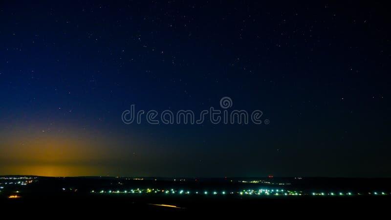 Vista nocturna de una ciudad, de un cielo por completo de estrellas y de una luz del sol en la puesta del sol imagenes de archivo