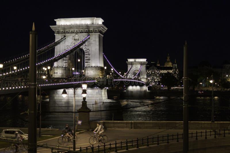 Vista nocturna del puente de cadena con los ciclistas que caminan las calles de Budapest, Hungría foto de archivo libre de regalías