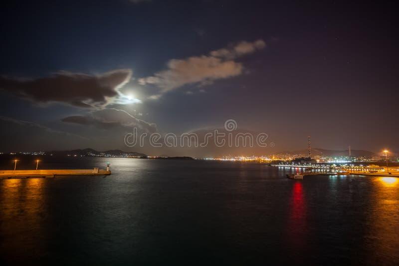 Vista nocturna del puerto de Atenas Pireo con la luna ocultada por las nubes fotos de archivo libres de regalías