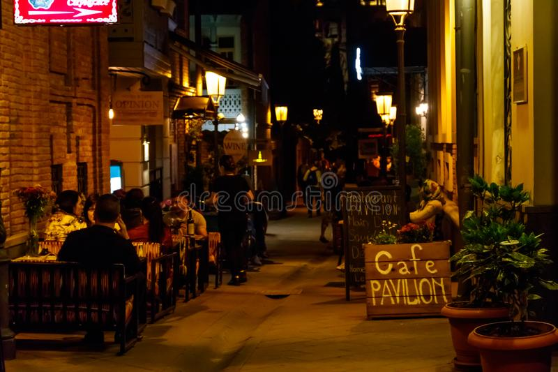 Vista nocturna a la calle estrecha con los cafés al aire libre en la ciudad vieja del distrito histórico de Tbilisi, Georgia imagen de archivo libre de regalías
