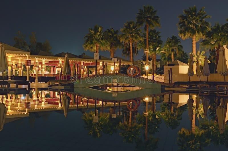 Vista nocturna que sorprende del área tropical del hotel de lujo con la piscina, la palmera e iluminaciones hermosas de la noche fotografía de archivo libre de regalías