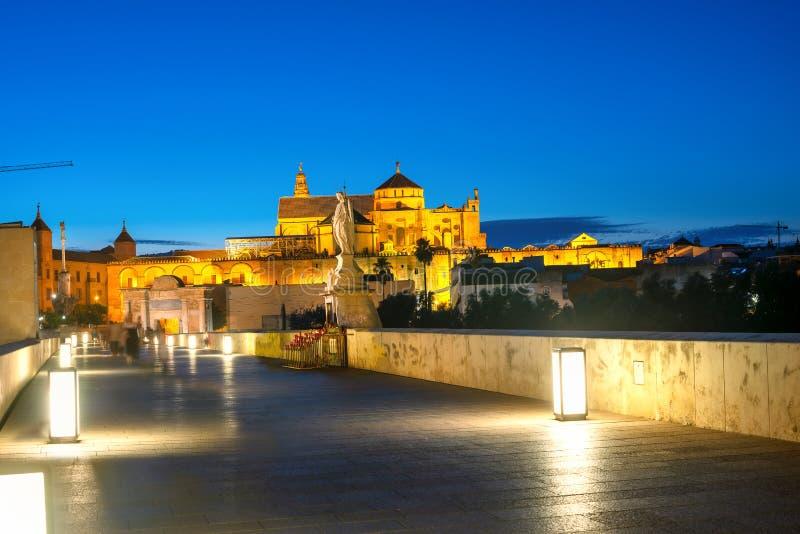 Vista nocturna a través del puente romano sobre el río Guadalquivir de la Gran Mezquita de Córdoba. Andalucía, España imagen de archivo