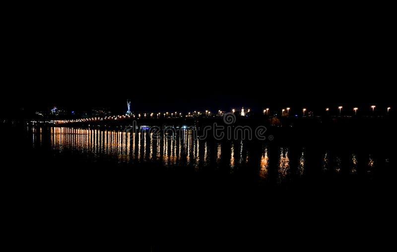 Vista notturna del ponte Paton sull'ampio fiume Dnieper e le luci della riva destra di Kiev Le lanterne di un immagine stock libera da diritti