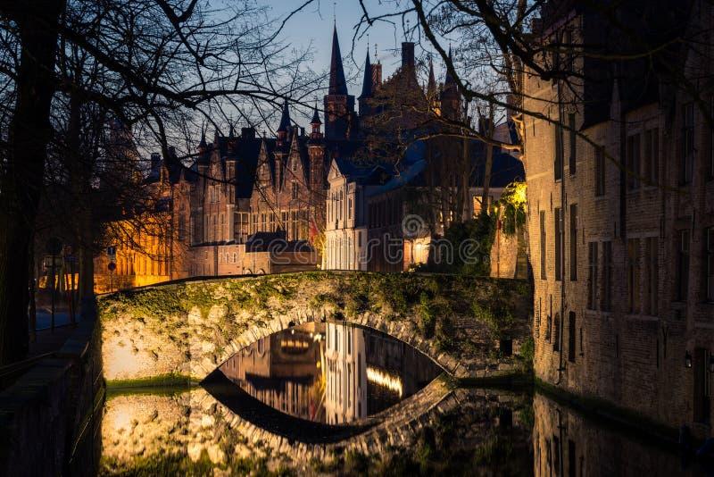Vista noturna de Brugge com canal tradicional, ponte de pedra, árvores e arquitetura, Bélgica foto de stock