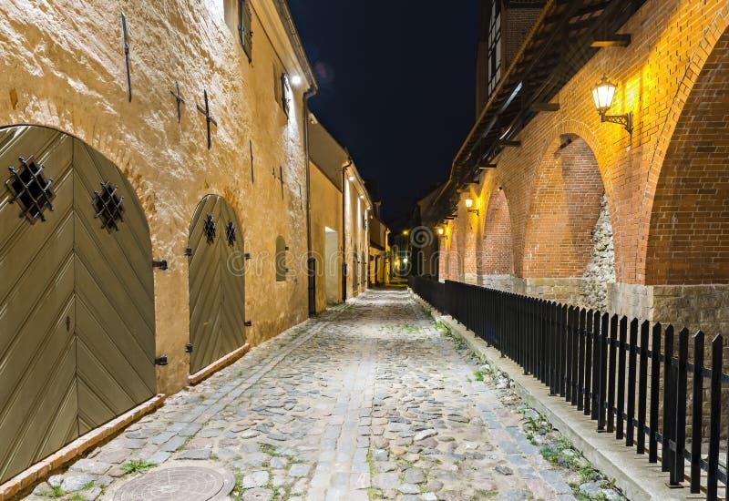Vista noturno na rua medieval estreita com a parede antiga da fortaleza, Riga, Letónia imagem de stock