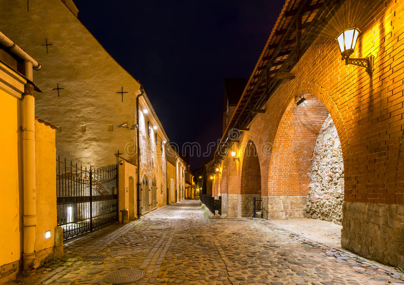 Vista noturno na rua medieval estreita com a parede antiga da fortaleza, Riga, Letónia fotografia de stock royalty free
