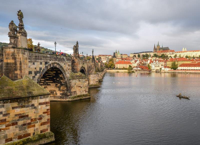 Vista nuvolosa drammatica di autunno del fiume della Moldava, di Charles Bridge, della st Vitus Cathedral, castello di Praga e di fotografia stock libera da diritti