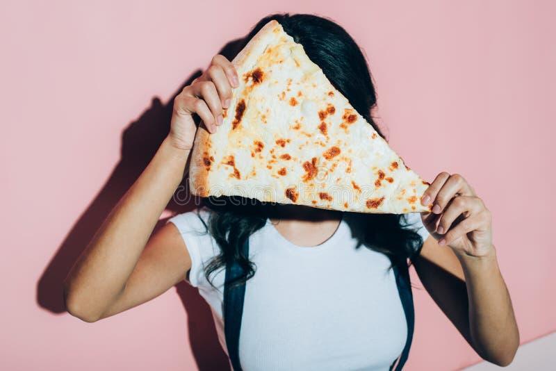 vista obscurecida da cara da coberta da mulher com parte de pizza foto de stock royalty free