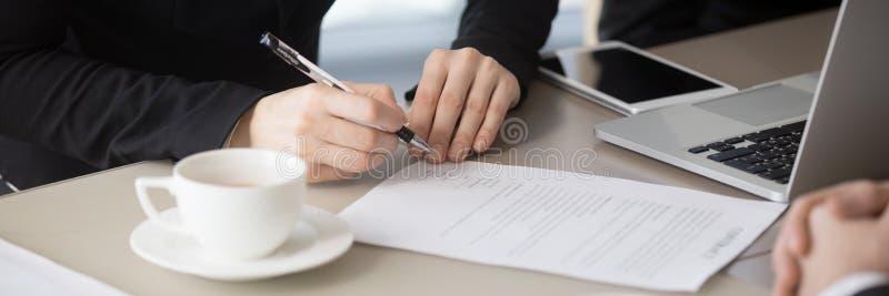Vista orizzontale del primo piano delle mani della donna di affari che firmano la carta legale del contratto fotografie stock