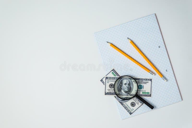 Vista ou flatlay superior da folha vazia do caderno da escola com lápis e dólares e lupa imagens de stock royalty free