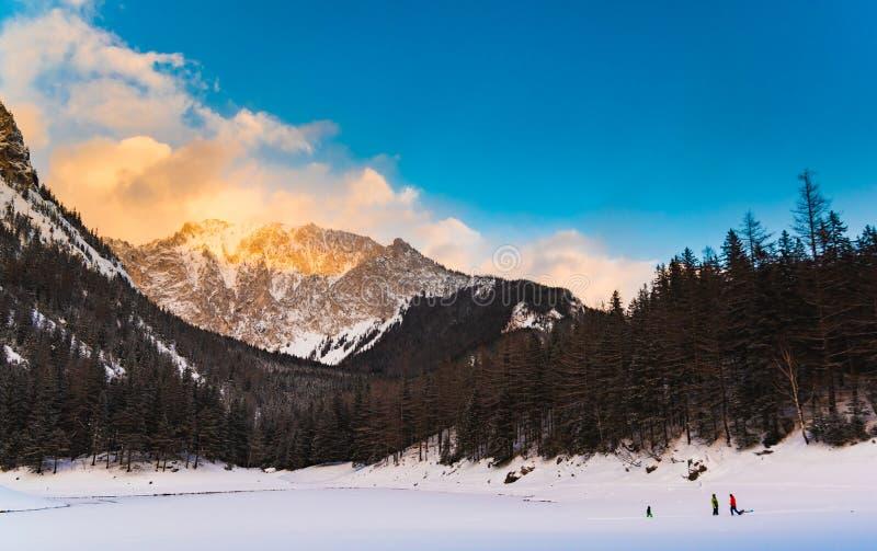 Vista pacifica della montagna sul lago verde Lago congelato in inverno durante il tramonto con picco di montagna sullo sfondo fotografie stock libere da diritti