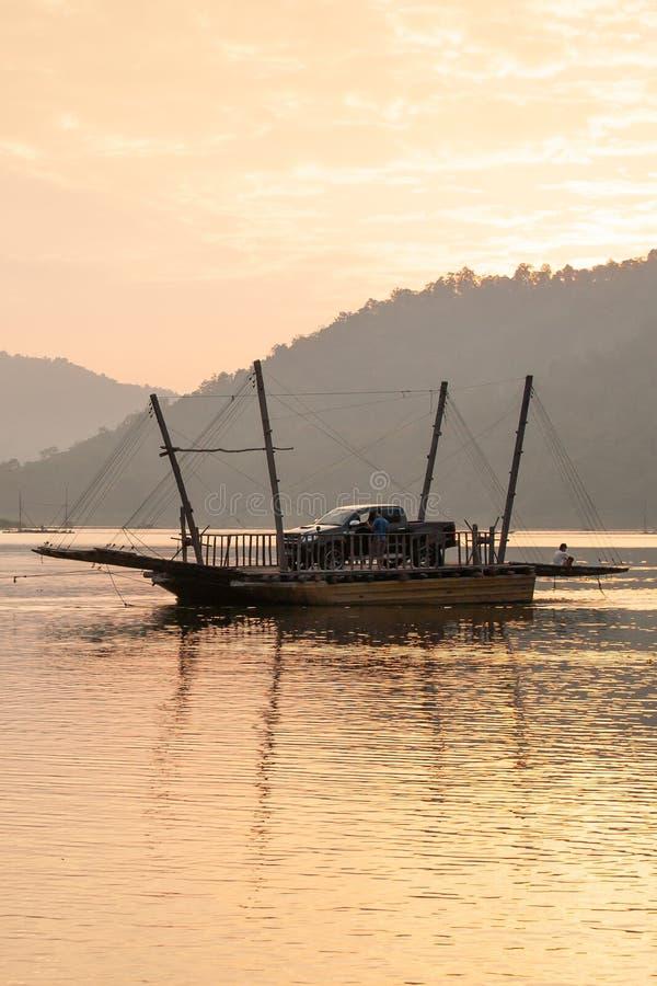 Vista pacifica, turisti e veicolo sul traghetto locale nel lago Sirikit, Nan Province, Tailandia Viaggiando al tempo di tramonto  immagini stock
