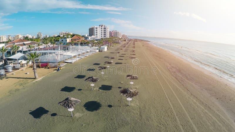 Vista panorámica aérea de la playa en los parasoles de la ciudad y de la paja de Larnaca, Chipre fotografía de archivo libre de regalías