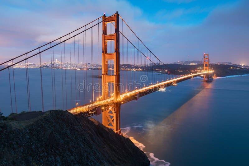 Vista panorámica clásica de puente Golden Gate famoso en luz de igualación hermosa en una oscuridad con el cielo azul y las nubes imagenes de archivo