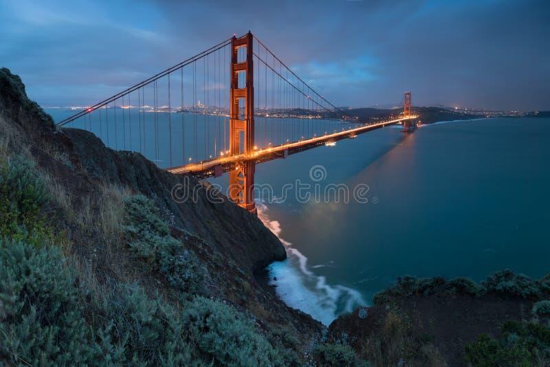 Vista panorámica clásica de puente Golden Gate famoso en luz de igualación hermosa en una oscuridad con el cielo azul y las nubes imagen de archivo