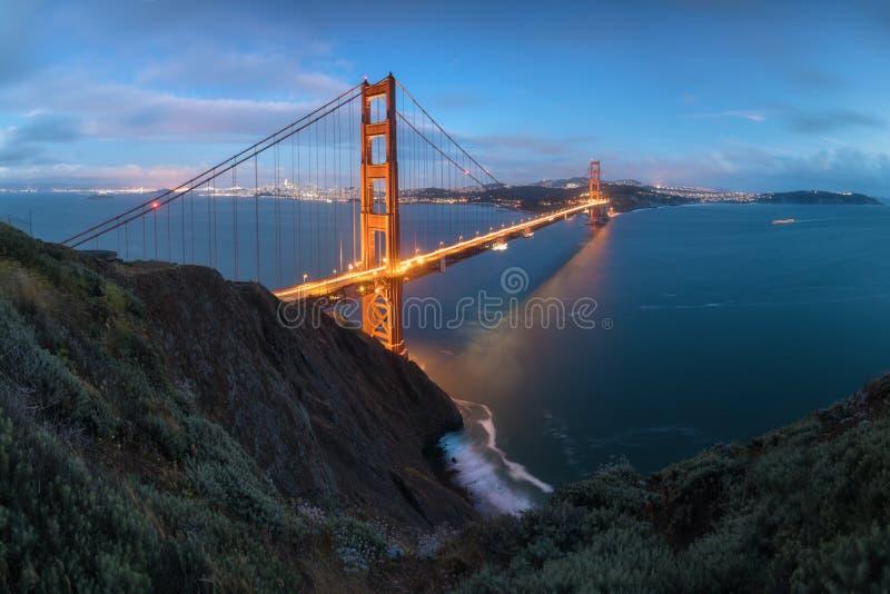 Vista panorámica clásica de puente Golden Gate famoso en luz de igualación hermosa en una oscuridad con el cielo azul y las nubes foto de archivo