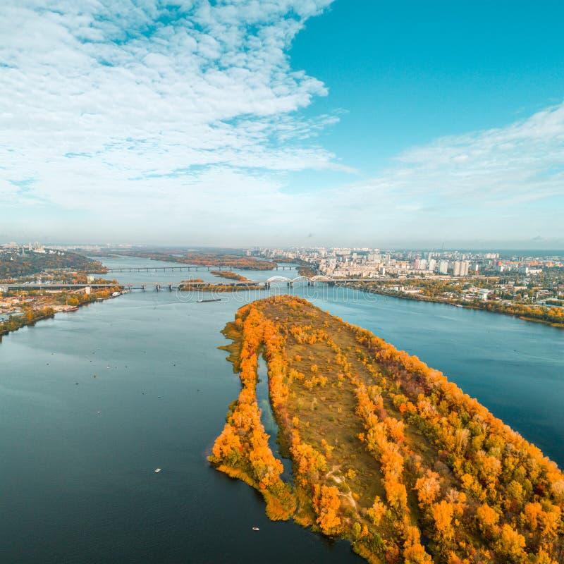 Vista panorámica de la ciudad de Kiev con el río de Dnieper y un área anaranjada grande del parque en el centro Silueta del hombr fotografía de archivo