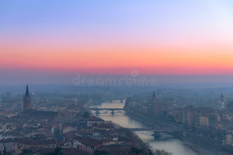 Vista panorámica de la ciudad de Verona y del río del Adigio con los puentes cubiertos con la niebla de igualación coloreada por  foto de archivo libre de regalías