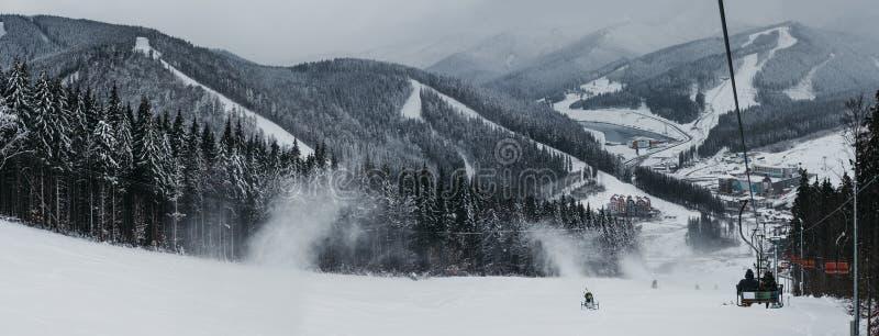 Vista panorámica de la estación de esquí de Bukovel del remonte, de la nieve, de las montañas y de los árboles en el fondo foto de archivo libre de regalías
