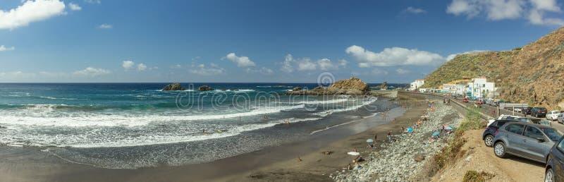 Vista panorámica de la playa de Aimasiga con la arena negra volcánica y las rocas solitarias que se pegan fuera de la espuma del  fotografía de archivo libre de regalías