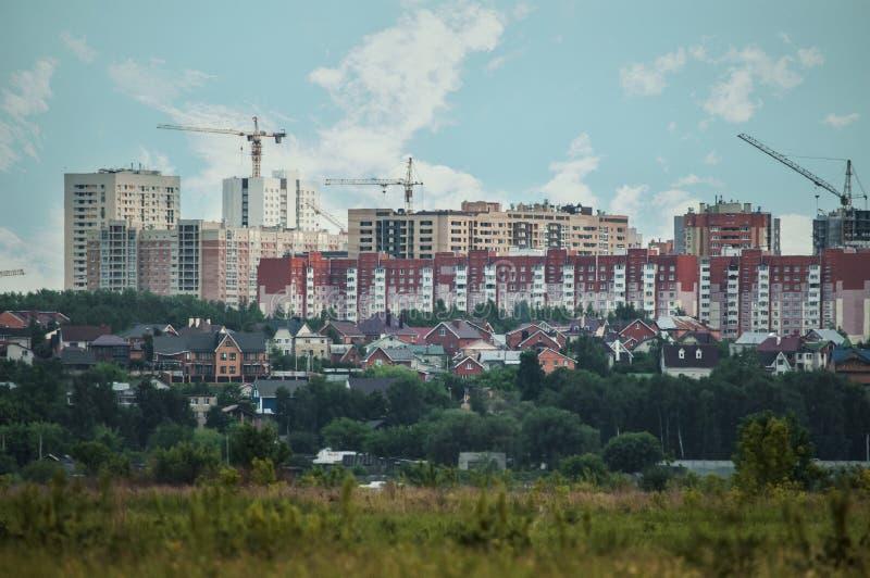 Vista panorámica de los edificios de la ciudad: edificios rojos de gran altura y casas de cintura baja entre el verdor foto de archivo libre de regalías