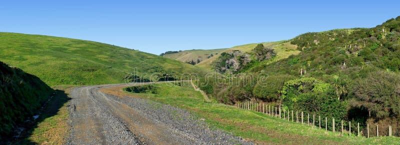 Vista panorámica de un camino a través de Rolling Hills con el bushland nativo fotos de archivo
