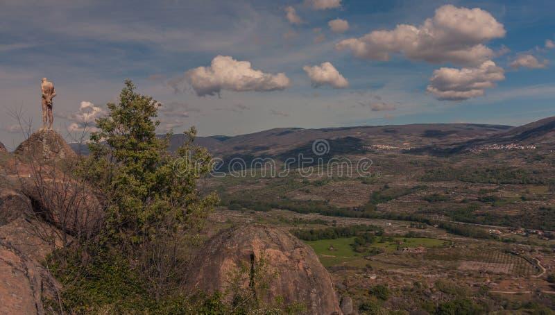 Vista panorámica de un valle y de una escultura en algunas rocas foto de archivo