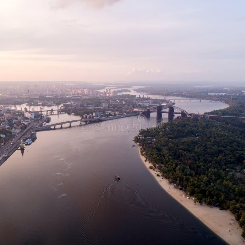 Vista panorámica de una ciudad moderna con un río, un puente inacabado y una pieza del parque de la ciudad foto de archivo libre de regalías