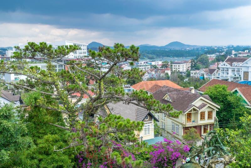 Vista panorámica del árbol verde con las flores y el tejado de casas con el cielo antes de la lluvia foto de archivo