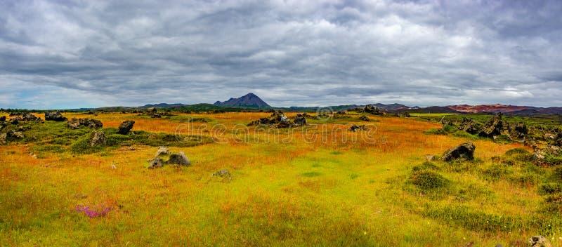 Vista panorámica del campo de lava cerca del lago Myvatn, de la ciudad Reykjahlid, y de los volcanes Hverfjall y Krafla en Island foto de archivo
