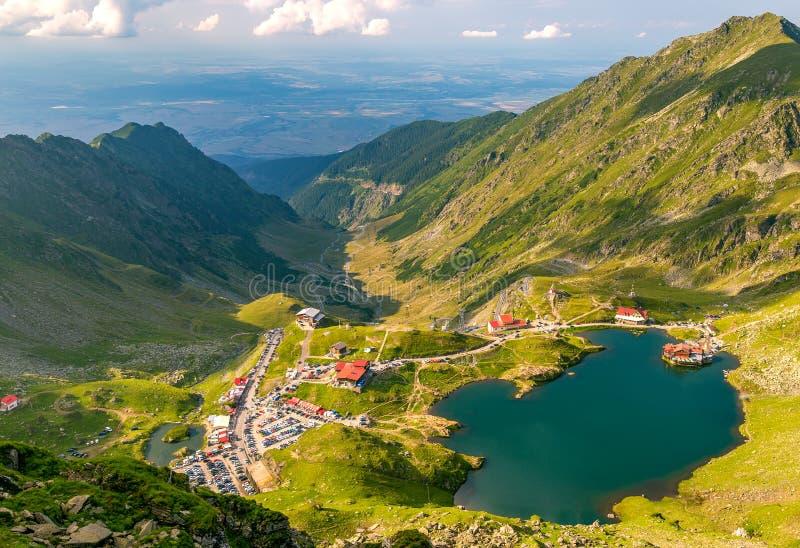 Vista panorámica del lago glacial Balea con el camino de Transfagarasan en la mayoría del lugar famoso de Rumania imagen de archivo libre de regalías
