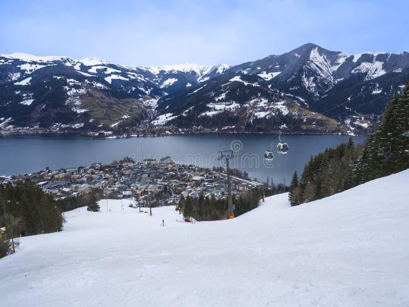 Vista panorámica del paisaje hermoso del invierno en las montañas con el lago, las cuestas claros de la nieve, cabinas del remont foto de archivo