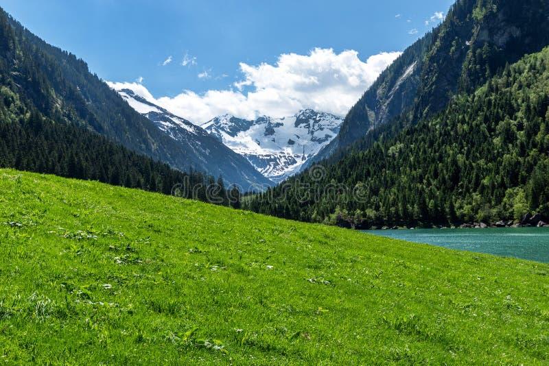 Vista panorámica del paisaje idílico de la montaña en las montañas con el prado verde fresco y los picos de montaña cubiertos nev fotografía de archivo