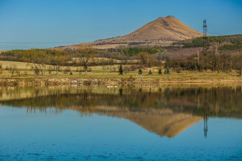 Vista panorámica del paisaje rural con una colina y un lago imagen de archivo