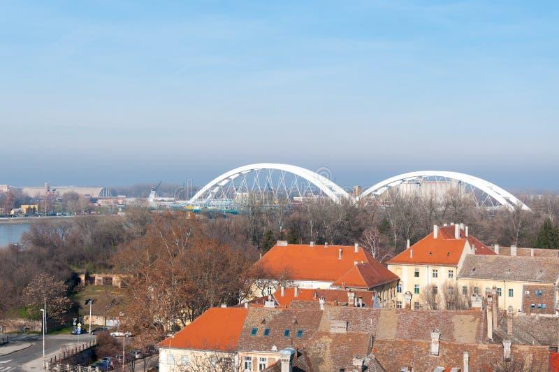 Vista panorámica del paisaje urbano de Novi Sad, de Serbia con dos puentes, el río Danubio y la parte de la fortaleza de Petrovar fotos de archivo