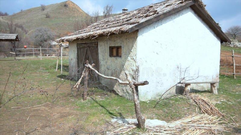 Vista panorámica del pueblo Barco de madera negro dilapidado viejo con una casa de un piso, un pozo y una colina De madera viejo imágenes de archivo libres de regalías