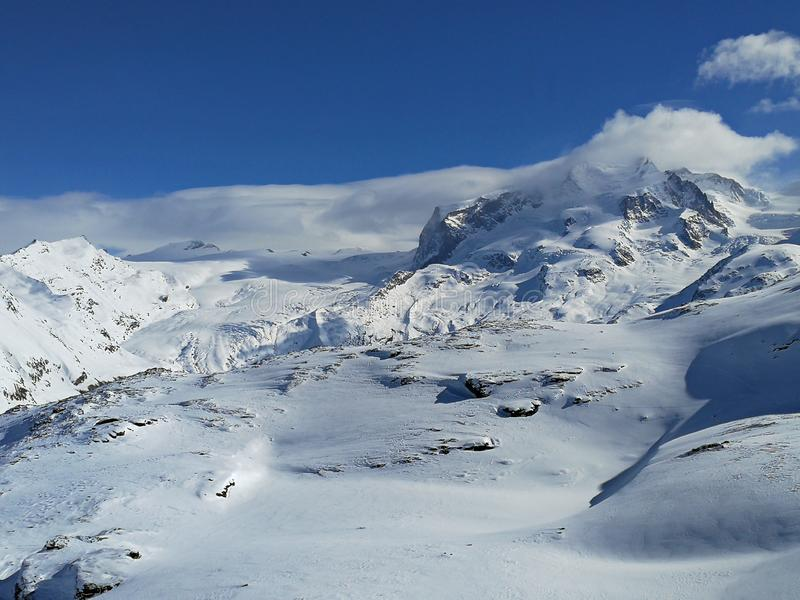Vista panorámica hermosa de montañas coronadas de nieve con las cuestas del esquí en las montañas suizas cerca de Zermatt, en el  imagenes de archivo