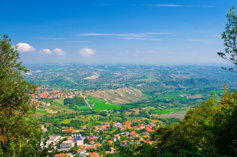 Vista panorámica superior aérea del paisaje con el valle, las colinas verdes, los campos y los pueblos de la república San Marino fotografía de archivo