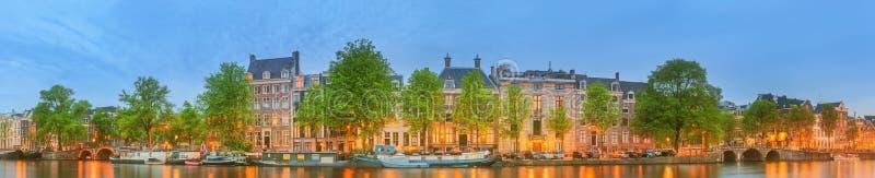 Vista panorámica y paisaje urbano de Amsterdam con los barcos, los edificios viejos y el río de Amstel, Holanda, Países Bajos foto de archivo libre de regalías