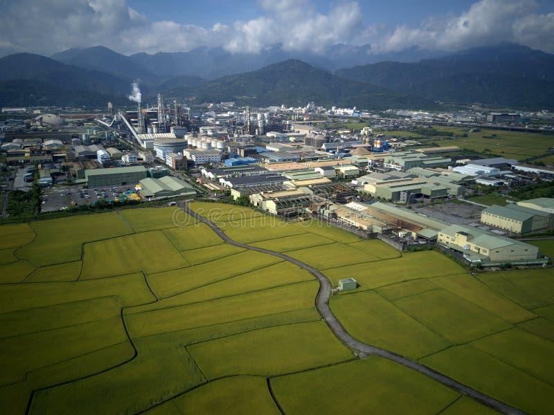 Vista panorâmica aérea de uma fábrica com as chaminés de fumo por almofadas de arroz verdes em Yilan Ilan imagens de stock