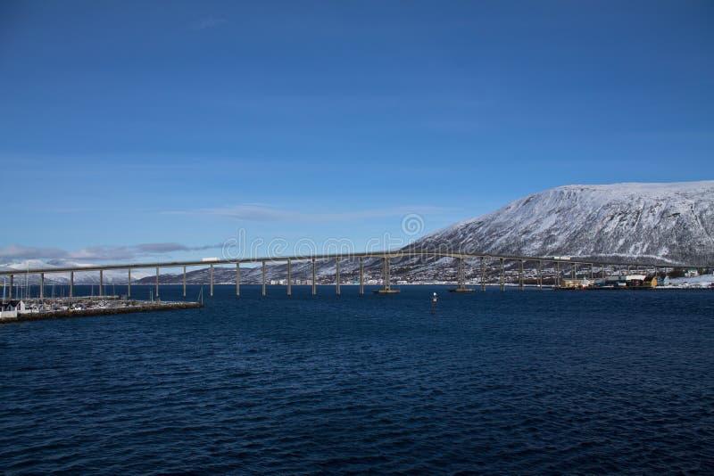 Vista panorâmica bonita do barco na paisagem de Tromso com montanhas nevado e ponte no céu azul ensolarado, Noruega imagens de stock royalty free